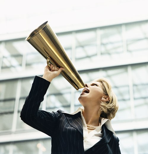 Stock Photo: 1598R-9976327 Businesswoman Shouts Through a Golden Megaphone