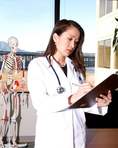 Stock Photo: 1598R-9976439 Female doctor writing on pad, close-up
