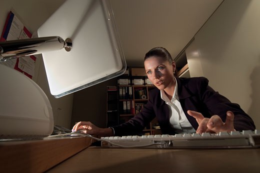 Stock Photo: 1598R-9976440 Suspicious Businesswoman Sitting in an Office Using a Computer