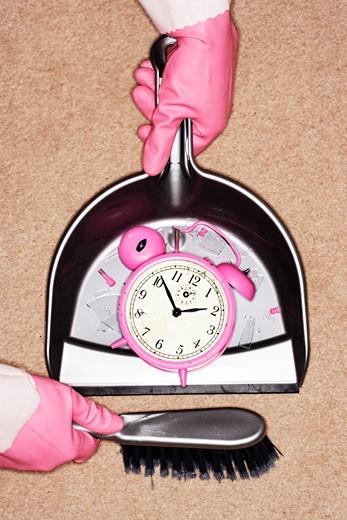 Stock Photo: 1598R-9976476 Woman sweeping up broken bell alarm clock, close-up