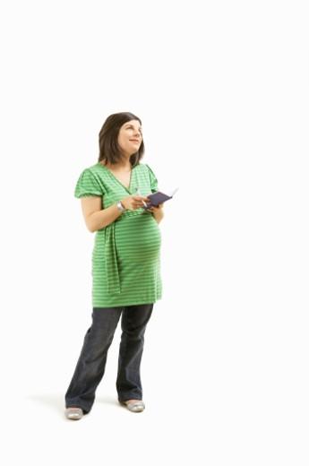 Stock Photo: 1598R-9977108 Pregnant woman holding diary, studio shot