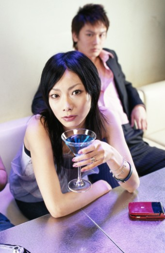 Young woman at bar, young man in background, portrait : Stock Photo