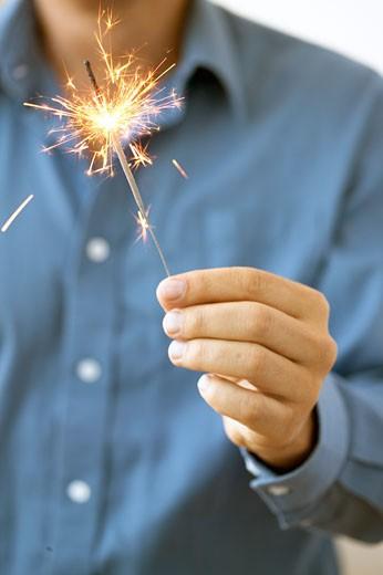 Man holding sparkler : Stock Photo