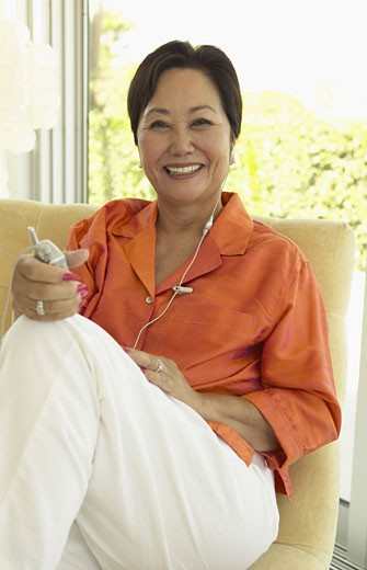 Mature Woman Sits in a Armchair at Home Listening to Her Mobile Phone With a Headset : Stock Photo