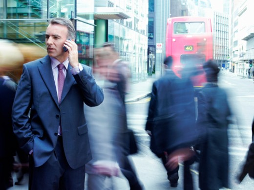 Stock Photo: 1598R-9978143 Businessman Standing with his Hand in his Pocket, Using a Mobile Phone with Blurred People and a Bus in the Background