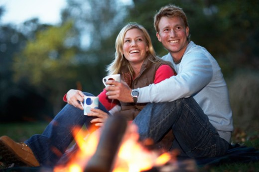 Young couple sitting by fire holding mugs, smiling : Stock Photo