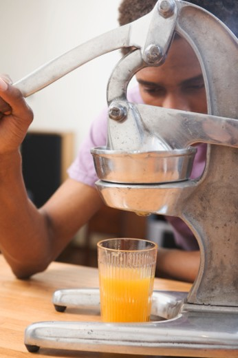 Stock Photo: 1598R-9978292 Man making orange juice. close-up of juicer