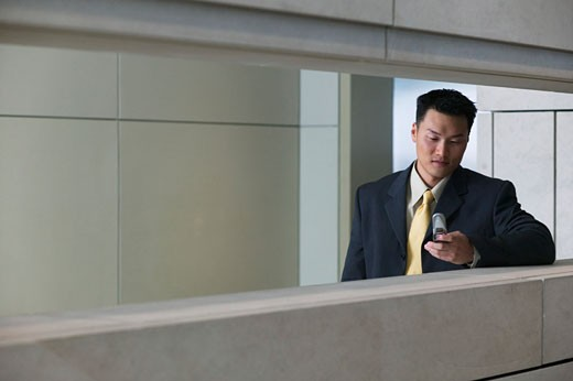 Businessman in hallway with mobile phone : Stock Photo