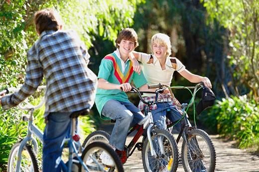 Stock Photo: 1598R-9978785 Three boys (9-13) on bikes, smiling