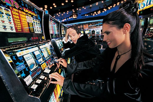 Stock Photo: 1598R-9978843 Male Gambler Gazing at a Woman Sitting at the Fruit Machines
