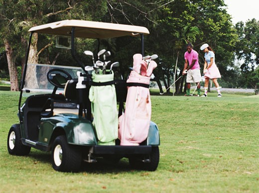 Couple practising golf shots on golf course, golf cart in foreground : Stock Photo