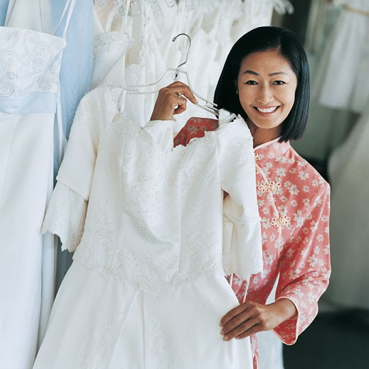 Stock Photo: 1598R-9979082 Smiling Young Bride Holding a Wedding Dress in a Clothes Shop