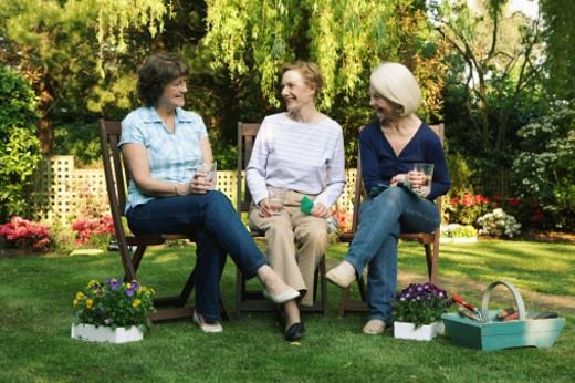 Stock Photo: 1598R-9979103 Three senior women sitting in garden holding drinks, smiling