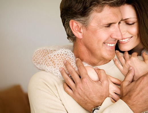 Man and woman hugging indoors : Stock Photo