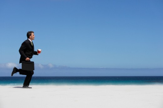 Businessman Running on a Beach Holding a Disposable Cup : Stock Photo