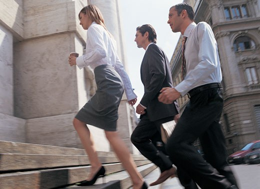 Three Businesspeople Walk Determinedly Up Stone Steps : Stock Photo