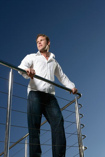 Stock Photo: 1598R-9980645 Young man on balcony looking away