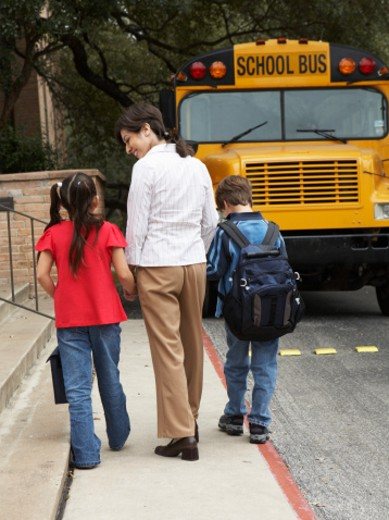 Teacher walking with boy and girl (8-9) to school bus, rear view : Stock Photo