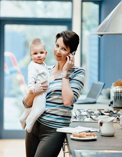 Portrait of a Woman Standing by a Kitchen Counter Holding Her Baby and Talking on Her Mobile Phone : Stock Photo