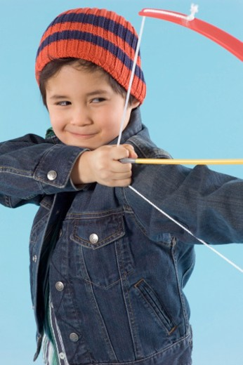Stock Photo: 1598R-9981567 Young Boy Wearing a Denim Jacket and a Beanie Hat Playing With a Bow and Arrow
