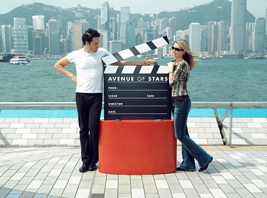 China, Hong Kong, couple by giant 'Avenue of Stars' clapperboard : Stock Photo