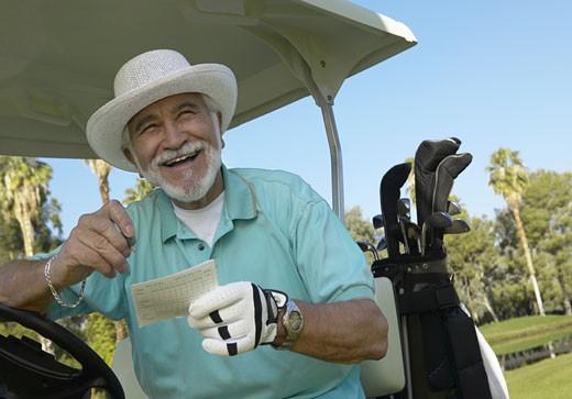 Senior Man Sitting on a Golf Cart Holding a Scorecard : Stock Photo