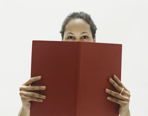 Woman Stands Looking Over a Red Book She is Holding : Stock Photo