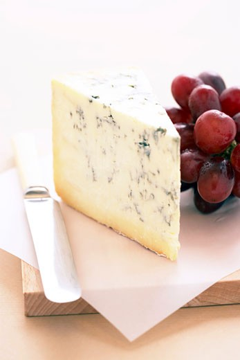 Stock Photo: 1598R-9982725 Wedge of Stilton cheese and red grapes on cheese board, close-up