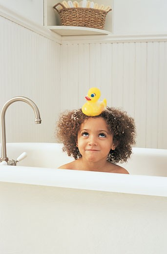 Young Girl Having a Bath Looking Up at a Rubber Duck on Her Head : Stock Photo