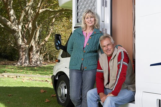 Mature couple by motor home in park, portrait : Stock Photo