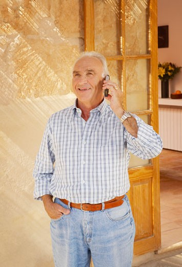 Stock Photo: 1598R-9983033 Senior man using cell phone outside house