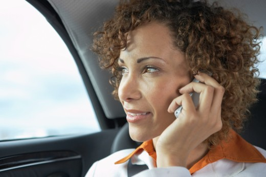 Stock Photo: 1598R-9983208 Business woman sitting on back car seat, talking on phone, close-up