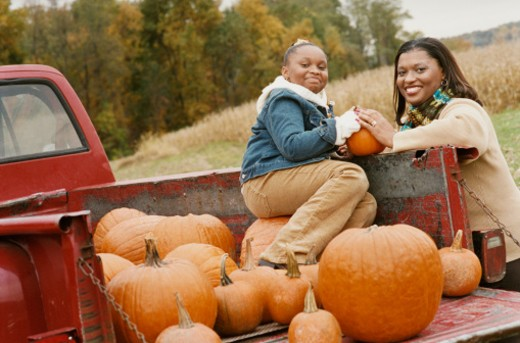 Stock Photo: 1598R-9983545 Mother and Daughter Holding a Pumpkin, Daughter Sitting in a Red Pick up Truck
