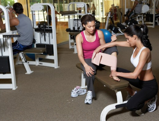 Woman wrapping bandage on woman's leg in gym : Stock Photo