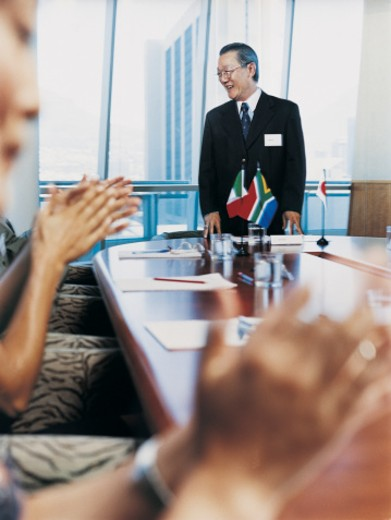 Smiling Ceo Receiving Applause Standing at the End of a Table in a Conference Room : Stock Photo
