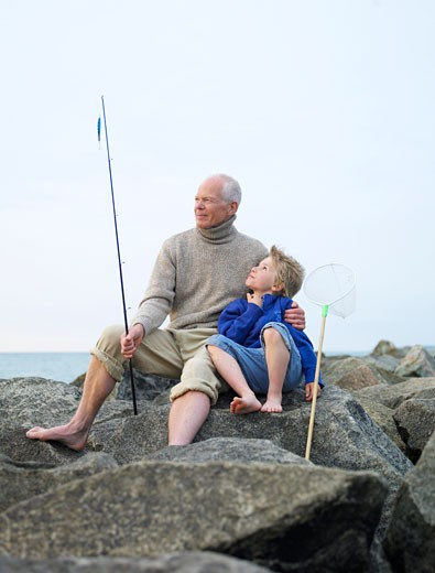 Grandfather sitting on rocks with grandson (4-6) holding fishing rod : Stock Photo