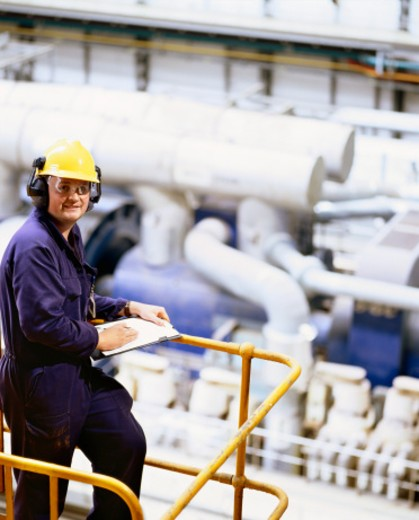 Worker Wearing Protective Clothing and Holding a Clipboard in an Industrial Plant : Stock Photo