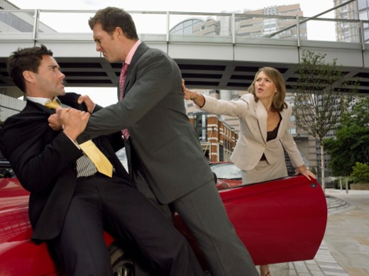Businessmen Fighting on the Bonnet of a Sports Car and a Businesswoman Stopping Them : Stock Photo