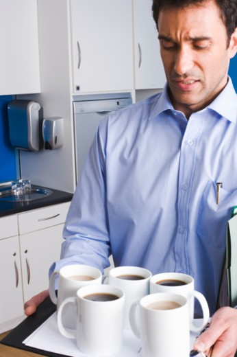 Stock Photo: 1598R-9984734 Businessman carrying tray of mugs in kitchen