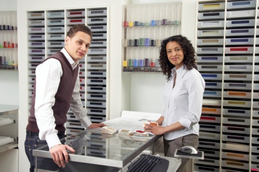 Man and woman selecting colour samples in shop, smiling, portrait : Stock Photo