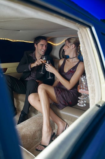Stock Photo: 1598R-9986062 Young couple drinking champagne in back of limousine, laughing