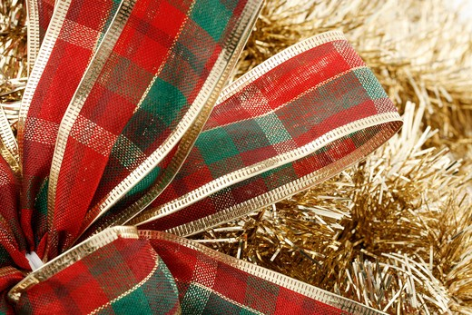 A red, green and gold bow against a gold garland background. : Stock Photo