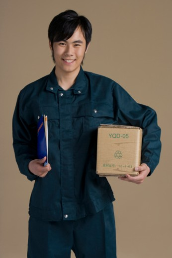 Chinese courier holding box and packages, portrait : Stock Photo