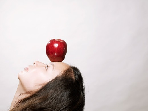 Young asian woman balancing red apple on forehead : Stock Photo