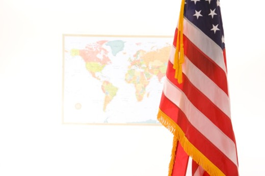 Close up of an American flag with a world map in background : Stock Photo