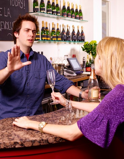 Stock Photo: 1598R-9988798 Barman refusing drinking woman drinks