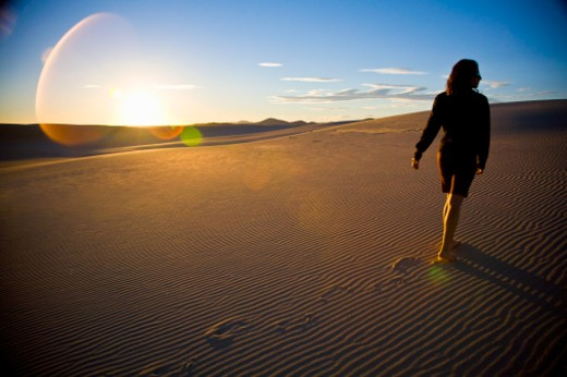 Wind-rippled sand dunes meet blue sky in New South Wales, Australia.  Young woman climbs to the top, leaving footprints int he sand, as the sun sets. : Stock Photo