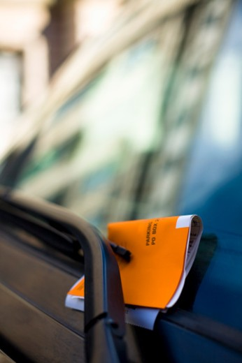 Orange parking ticket restrained by windshield wiper with reflections of New York skyscrappers on windshield. : Stock Photo