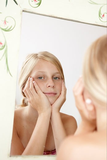 Blonde girl looking at her reflection in a mirror. : Stock Photo