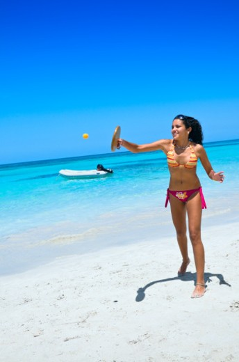 Stock Photo: 1598R-9989948 Attractive young woman playing  in a Caribbean white sand beach